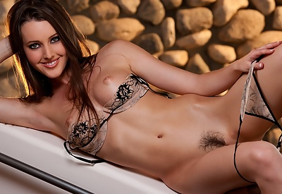 Picture Gallery of Erica Ellyson busty brunette sexy lingerie strip-tease by stone wall