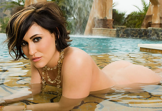 Ryan Keely, in a red string bikini, rests half-submerged in the waters of a Roman aqueduct-styled pool!