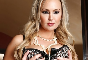 Blonde bombshell Abbey Brooks shows off her curves while stripping from her lingerie and thigh highs/