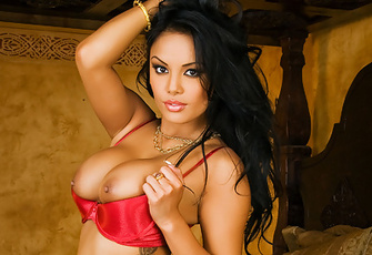 Justene Jaro's dark nipples tantalizingly peak over her red bra as she poses half-nude on the edge of a high four-post bed.