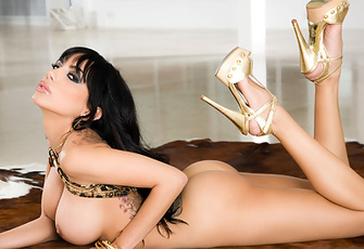 Lela Star pulls apart the straps of her gold bikini, letting it fall away from her perfect boobs and hips as she poses nude on top of a cowhide rug.