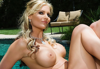 Busty blonde Phoenix Marie stretches out nude on top of a poolside rocky ledge to relax and sunbathe in the tropical Pacific sun!